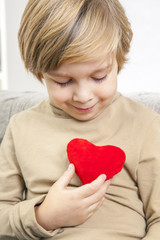 Сute young boy with a red heart