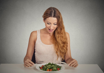 young woman eating green salad on grey wall background