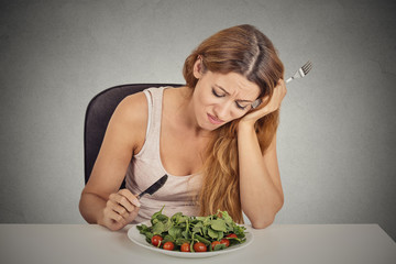 sad displeased young woman eating salad grey wall background