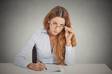 businesswoman with glasses sitting at desk looking at you