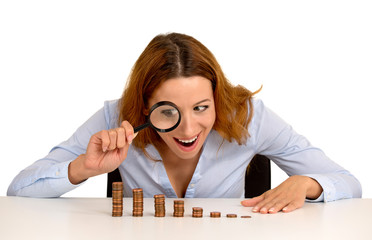 woman looking at growing stack of coins through magnifying glass