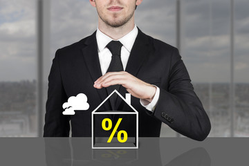 businessman holding protective hand above building percentage sy