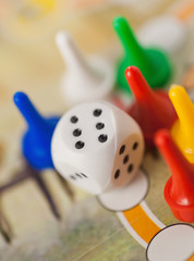 white dice cube near multicolored counter on game field
