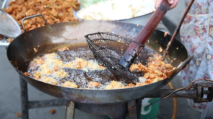 Human hand cooking deep fried ,boiling in oil