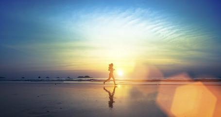 Young girl running along the beach.