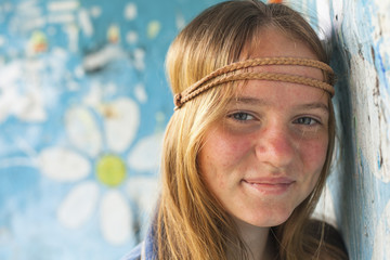 Young cute girl hippie, old dirty wall on the background.