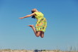 Young woman in summer dress jumping