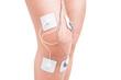 Electrostimulator massager on her knee. Injury athlete. - 76121170