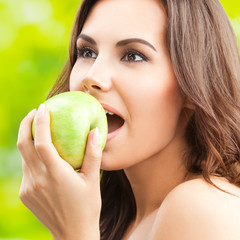 Woman eating green apple, outdoor