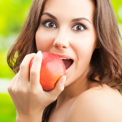 Woman eating red apple, outdoor
