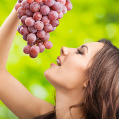 Young woman with grapes, outdoor