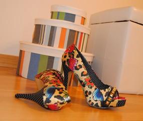 Zapatos de tacón estampados junto cajas de colores