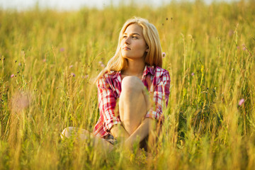 Happy blonde girl sitting on grass