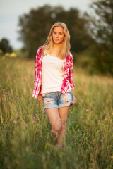 Beautiful girl standing among the grass of the field