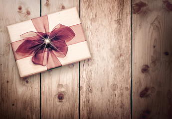 Present box with brown ribbon on wooden background.