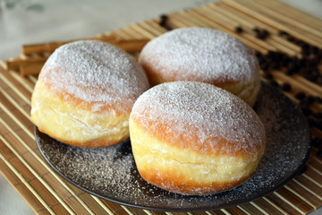 Donuts with powdered sugar on the brown plate