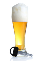 Composition with car key and glass of beer, isolated on white