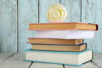 Books with flower on wooden background