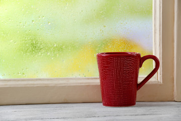 Cup of hot drink on windowsill on rain background