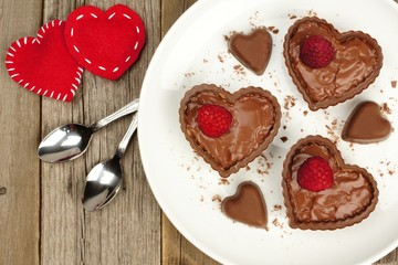 Heart shaped chocolate dessert cups with pudding and raspberries