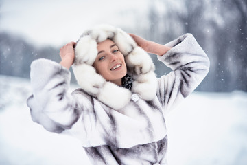Woman having fun on the snow in winter forest