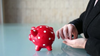 Businesswoman put coins into red dotted piggy bank, saving