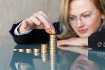 Businesswoman in glasses building coin columns