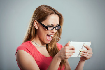 Studio shot of young woman screaming while using digital tablet.
