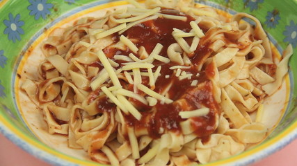 Cheese being added to tomato sauce on pasta.