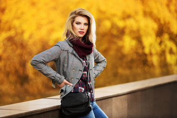 Young fashion blond woman in autumn city park