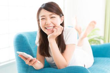 部屋でスマートフォンを見る女性