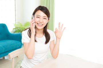 部屋で電話をする女性