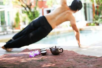 Man doing Yoga and pot of tea