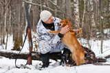 hunter with his dog during the rest on winter hunting