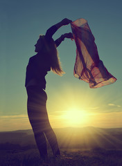 Girl with a scarf in the sunset