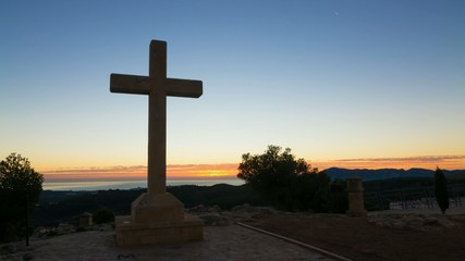 Huge cross against the background of a sunrise