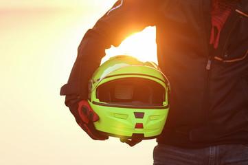 biker man helmet in hand sunset