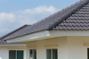 black roof tiles on house with blue sky