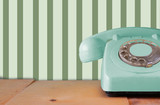 Retro pastel mint telephone on wooden table and abstract retro g
