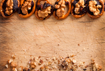 pretzels with chocolate and nuts on wooden background