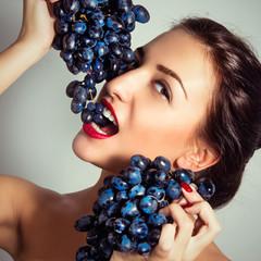 Портрет красивой сексуальной женщины с виноградом