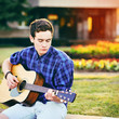 Young hipster man playing guitar in a park