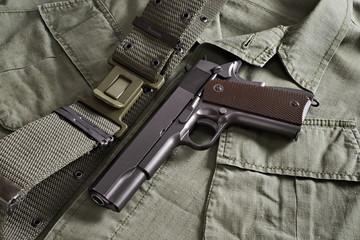 Colt pistol and belt lie on military jacket