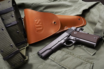 Colt gun pistol, holster and belt lie on military jacket