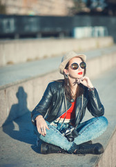 Young fashion beautiful girl in leather jacket with retro camera