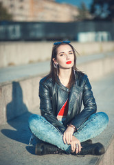 Young fashion beautiful girl in leather jacket outdoor