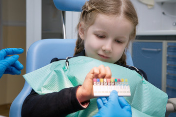 the child dental picks colored fillings on clinic