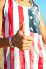 It's alright! Young girl in american shirt showing thumb up.