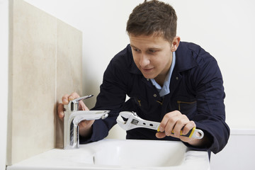 Male Plumber Working On Sink Using Wrench