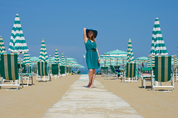 Portrait of standing girl in hat on the seaside path.